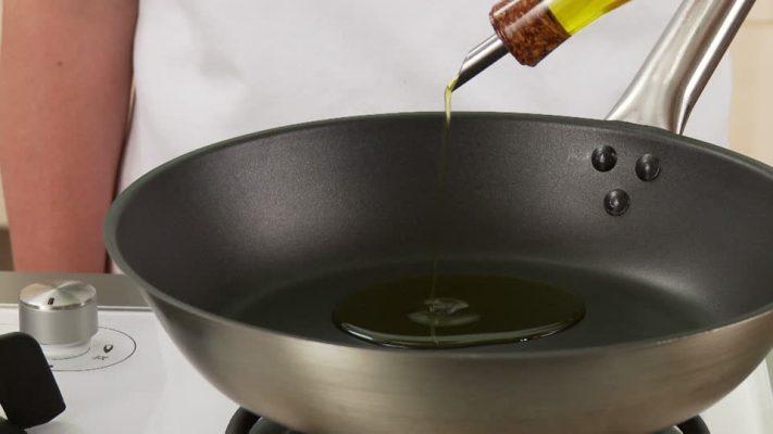vertiendo aceite de oliva en sartén